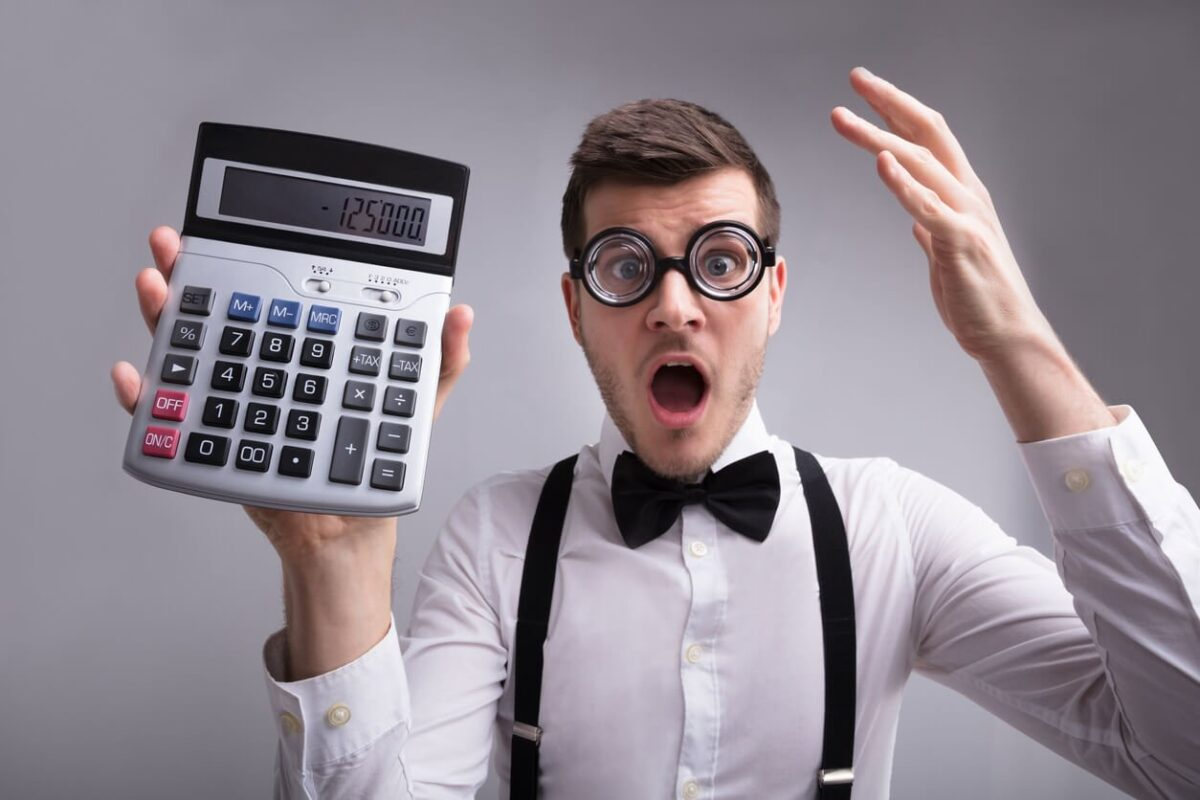 Get Real About Mortgages - Surprised man holding a calculator