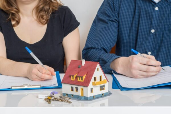 Spring Cleaning Your Marriage: What Happens To Your Home?- two people signing paperwork with a little house in the middle